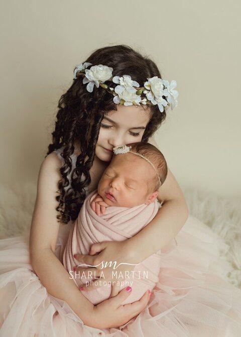 big sister snuggling newborn baby sister flower crown