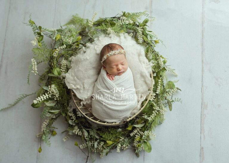 newborn baby wrapped in prop with flowers