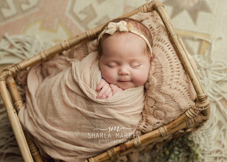 newborn baby in wicker crib